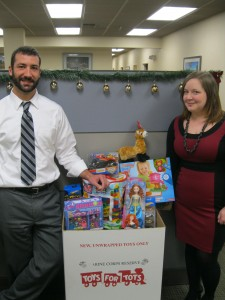 Domenick DelRosso (left) and Mistie Knapp (right) with gifts gathered by the Judelson, Giordano & Siegel staff and partners for the annual Toys for Tots campaign.