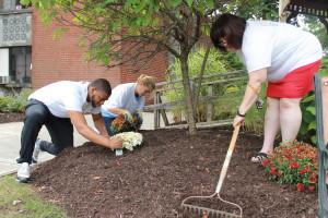 United Way loaned executives Kyle Richardson, left, Linda Shuback and Haydee Furman work on mulching and planting activities.