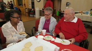 Anjoule LeLaMartin of the Newburgh School District talks about cookie frosting options with Glen Arden residents Esther and Martin Schwager during Junior Leadership Orange's recent visit to Glen Arden.